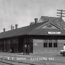 Image of N1299 - Second Southern Pacific passenger station, end of Cass St. at Sheridan St., Roseburg. Douglas County Flour Mill in rear.