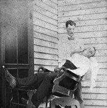 Image of N13529 - REMARKS:John Tuliek and James Porterfield. One of them is giving the other one (sitting in a barber chair) a shave, ca. 1890. Roseburg, Oregon?  OBJECT DATE:ca. 1890
