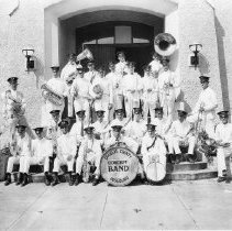 Image of N14113 - COUNT:2  REMARKS:Douglas County Concert Band, Roseburg, OR, ca 1930. Man sitting at far right in front row with snare drum is Jefferson Ford Singleton. Sittting in front of the Roseburg Armory building.  OBJECT DATE:ca 1930