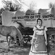Image of N15202 - COUNT:2  REMARKS:Centennial wagon with female passenger in period garb; horse grazing nearby. 1959.