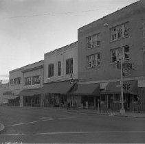 Image of N15211 - REMARKS:Blast damaged Jackson Street. Showing Montgomery Ward store, Judd's furniture, Watch repair, etc. Roseburg, OR, August 1959.