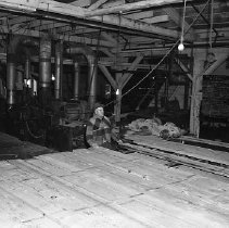 Image of N15369 - REMARKS:Interior of sawmill, showing worker feeding lumber through planer. Douglas County, OR; ca 1950s.  OBJECT DATE:ca 1950s