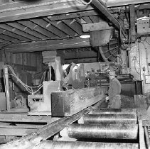 Image of N15381 - REMARKS:Log being sawn into lumber, mill interior with one worker shown. Douglas County, OR, ca l950s  OBJECT DATE:ca 1950s