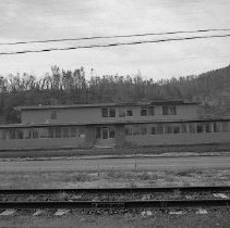 Image of N15415 - REMARKS:Office building of Roseburg Lumber Co. Exterior view with railroad tracks in foreground. Douglas County, OR, ca 1950s.  OBJECT DATE:ca 1950s