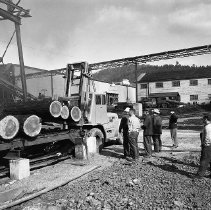 Image of N15470 - REMARKS:Logs being unloaded from self-loading log truck at sawmill, with several workers looking on. Douglas County, OR, ca 1950s.  OBJECT DATE:ca 1950s
