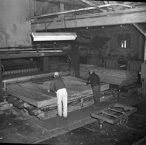 Image of N15480 - REMARKS:Veneer being fed by workers into dryer. Douglas County, OR, ca 1950s.  OBJECT DATE:ca 1950s