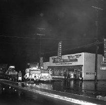 Image of N15661 - REMARKS:Fire Department pumping water out of drains on Stephens Street. Shows fire truck, men, Jack Fariss & Son Furniture Store. Roseburg, OR, 1955.