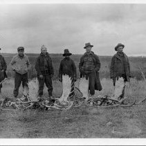 Image of N15693 - COUNT:2  REMARKS:Gus Peret (3d from left)with five unident. men standing with moose and elk racks. Alaska, 1919. Gus Peret Collection.