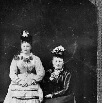 Image of N16060 - REMARKS:Two women in fancy dresses, ca 1870. Emma Bonebrake Harpham Erickson is at the right, and Mrs. Riggs is at the left. Douglas County residents. Tintype.