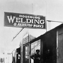 Image of N16406 - REMARKS:Roseburg Welding and Radiator Works, located on Main Street, Roseburg, OR, ca 1926. John Francis Ospald, the owner is standing at left.