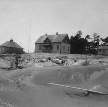 Image of N16460 - COUNT:2  REMARKS:Umpqua Life Saving Station, ca 1989. Shows the boat house and keepers house. Winchester Bay, OR.  OBJECT DATE:ca 1889