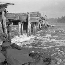 Image of N16502 - REMARKS:Destruction of the jetty after the flood of Dec. 23, 1964. Winchester Bay, OR.  OBJECT DATE:December 1964