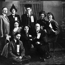 Image of N16585 - REMARKS:Roseburg Business people dressed up with wigs and false beards, 1913. Howard B. Church is standing, center. Minnie Clark is sitting in the center. B.W. Bates is at right. They are wearing Oregon Electric ribbons