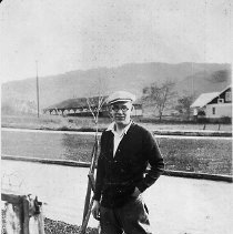 Image of N16592 - REMARKS:Charles Stanton standing on Commercial Street in Roseburg, OR, 1927. In front of the Wimer's house. Photo taken by Mr. Wimer. (they were friends). Stanton is ready to hike up mountain near the neighborhood.