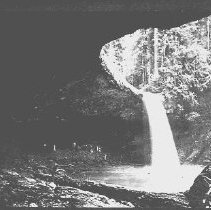Image of N16646 - REMARKS:Waterfall on the Coos Bay Wagon Road, ca 1903. Group of people standing under the over-hanging rock.  OBJECT DATE:ca 1903