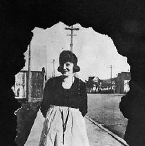 Image of N16665 - REMARKS:Woman standing on the street in Oakland, OR, ca 1918.  OBJECT DATE:ca 1918