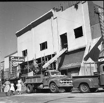 Image of N16821 - REMARKS:Roseburg, OR, after the blast of August 7, 1959. View shows workers cleaning up a building on Jackson Street by dumping debris from a second story window into a dump truck.