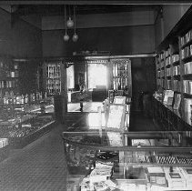 Image of N17070 - REMARKS:Interior view of Steiner & Chapman Drug Store showing shelves of books and glass display cases full of merchandise, ca 1910.  OBJECT DATE:ca 1910