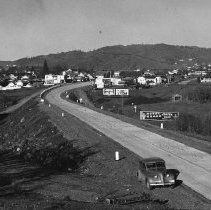 Image of N17123 - Highway 99 coming into Roseburg, Oregon, circa 1940.  View shows car pulled over on the side of the road (may be Gene Powell's - the photographer's).  Billboard advertising the Hotel Grand.