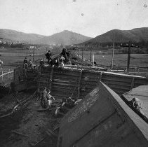 Image of N1916 - REMARKS:Wreck on S.P. Railroad at the Garden Valley crossing, view is looking south toward Roseburg. Sam Starmer in suit on top of freight car.  INSCRIPTION:n1917