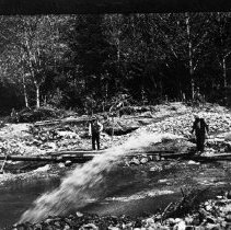 """Image of N3951 - REMARKS:Lee's Creek hydraulic mining, 1913. J.M. Martin at right; water just starting to flow through nozzle of """"giant"""". Monitor, Long tom, Myrtle Creek area"""