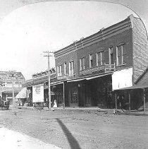 Image of N5 - View of East side of Sheridan St., between Cass & Lane. Includes a grocery store, a restaurant, a boarding house, a bakery, a confectionery & hardware store, ca. 1910. This business area would have been near the railroad depot. The tall flour mill at left was destroyed in the 1959 Roseburg Blast.  OBJECT DATE:ca. 1910