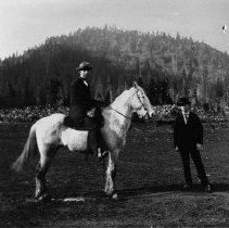 Image of N5785 - REMARKS:Unident. man on white horse and friend, Glendlae, Or. Wood piles and locomotive in background. ca. 1910.  OBJECT DATE:ca. 1910