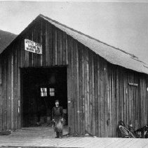 Image of N6125 - REMARKS:Exterior view of Myrtle Creek blacksmith shop; smith in doorway.