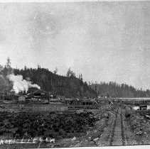Image of N6182 - REMARKS:View of Johnson's Mill, Reedsport, Oregon. A railroad spur track and the Umpqua River are at right; view is looking east.