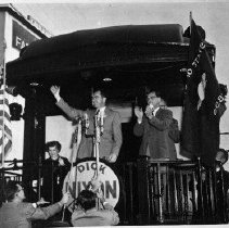 Image of N6247 - REMARKS:Richard Nixon campaigning for office in Roseburg from the rear of a train in 1952. Mrs. Nixon seated at left rear; Al Flegel at Nixon's left. The Farm Bureau building is left rear.