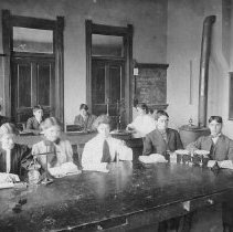 Image of N6285 - COUNT:2  REMARKS:Nine students seated at tables (chemistry class?). An unidentified school room shows a wall clock, black boards, lab equipment and a wood heater.
