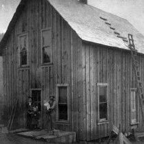 Image of N6449 - REMARKS:John Binder house in northwest part of Elkton, Oregon, under construction. At left is Mrs. John (Bessie Culy) Binder; the small girl is Anna Binder whose first husband was Ed Helms and her second husband was Forrest Fry; John Binder is holding Gilbert Binder. ca. 1907.  OBJECT DATE:ca. 1907