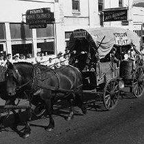 "Image of N7978 - REMARKS:A covered wagon drawn by a dark team advertising the Roseburg Pageant. The wagon has a sign reading ""Dixonville"" and ""Oregon or Bust."" the view shows the wagon heading south on Jackson Street; in the rear is Horn's Icecream Parlor and Percy Croft's Garage, etc."