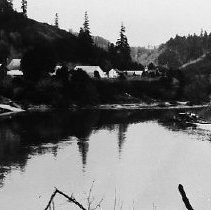 Image of N8756 - REMARKS:Ferry crossing Umpqua River at Scottsburg, Or. ca. 1930s. From south bank. View shows a number of buildings and town.  OBJECT DATE:ca. 1930s