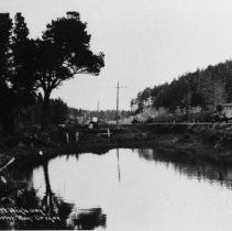 Image of N8815 - REMARKS:Highway 101 near Winchester Bay, Or. ca. 1929. Auto at right, water in center foreground.