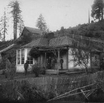Image of N9454 - COUNT:2  REMARKS:Mr. and Mrs. Emmons and family in front of their house in Leona, Oregon; 1901-1902. The house is a single-story wood-frame building with a bay window in front; there is a picket fence in the foreground, and a barn on a hill in the rear.