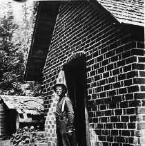 Image of N7168 - REMARKS:Will Q. Brown in the doorway of a brick building at Nickel Mountain Nickel Mine, Riddle, 1916.