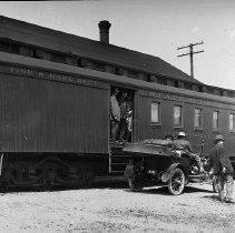Image of N7316 - REMARKS:The Oregon State Fish and Game Dept. Distributing Car, RAINBOW. The view shows a special railroad baggage car with an early automobile along side; fish fry were distributed to various points by this car.