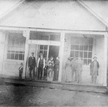 """Image of N7876 - REMARKS:The W.L. Cobb store at Wilbur, Oreg., ca. 1899. The sign between the porch pillars reads, """"Milwaukee---."""" The is a group of people on the porch.  OBJECT DATE:ca. 1899"""