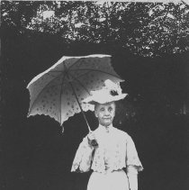 Image of N6037 - REMARKS:Lillie Moore standing out of doors wearing hand crocheted or embroidered dress, cape, hat and parasol. Outfit is now in the Lane House Collection of Douglas County Historical Society.