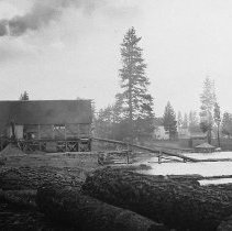 Image of N8589 - REMARKS:Unident. sawmill showing logs, pond, steam smoke stack, etc. May be Idaho?