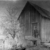 Image of N9110 - REMARKS:Peter Nash with a shake froe in front of his combination house and shop, a board and batten building, Elkton, Oregon. The present site is occupied by the city hall.