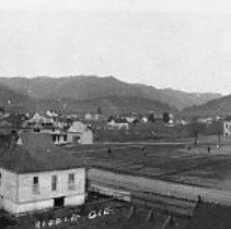 Image of N11843 - REMARKS:Panorama view of Riddle, Or. showing most of the town, the old school is at right of center with children on the baseball field, ca. 1907.  OBJECT DATE:ca. 1907