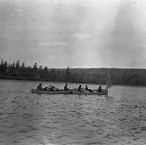 Image of NN144 - Two boats, one has sail, five men aboard.  Side view, closer, wide expanse of water, opposite tree-linked bank.  Alaska 1919.