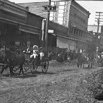 Image of NN402 - Parade on Jackson Street in early Roseburg with horse drawn floats through dirt streets.  Jay Golden photo collection