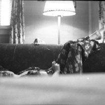 Image of N17527 - An unidentified woman sleeping on a couch with feet resting on back of couch. From the Weston Dailey Collection