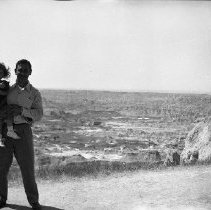 Image of N17555 - Weston Dailey holding a little girl.  An unidentified woman is seen in the background taking picture of the waves.