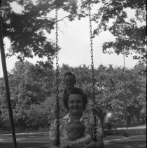 Image of N17569 - Unidentified woman holding a baby on a swing while an unidentified man stands behind her From the Weston Dailey Collection