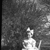 Image of N17606 - An unidentified little girl sitting on a chair by the bushes. From the Weston Dailey Collection