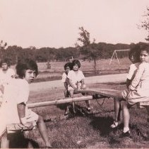Image of Young Girls Playing on See-Saws